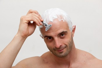 Young man shaving his head with razor blade